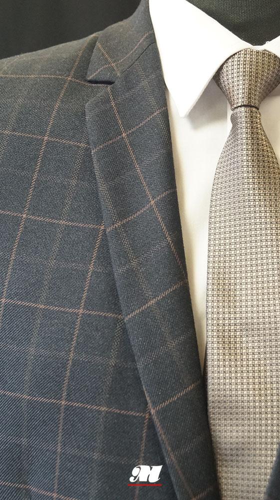 55c09afc010c5 Garnitur wykonany z powracającej do świata mody tkaniny w kratę, z  brązowymi, zamszowymi wykończeniami, dwoma rozcięciami oraz spodniami typu  slim.